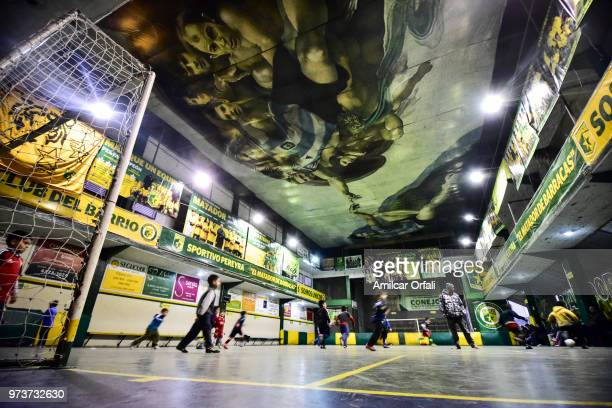 Kids play at the 5aside pitch of Sportivo Pereyra de Barracas club on June 13 2018 in Buenos Aires Argentina The mural was painted in the ceiling of...