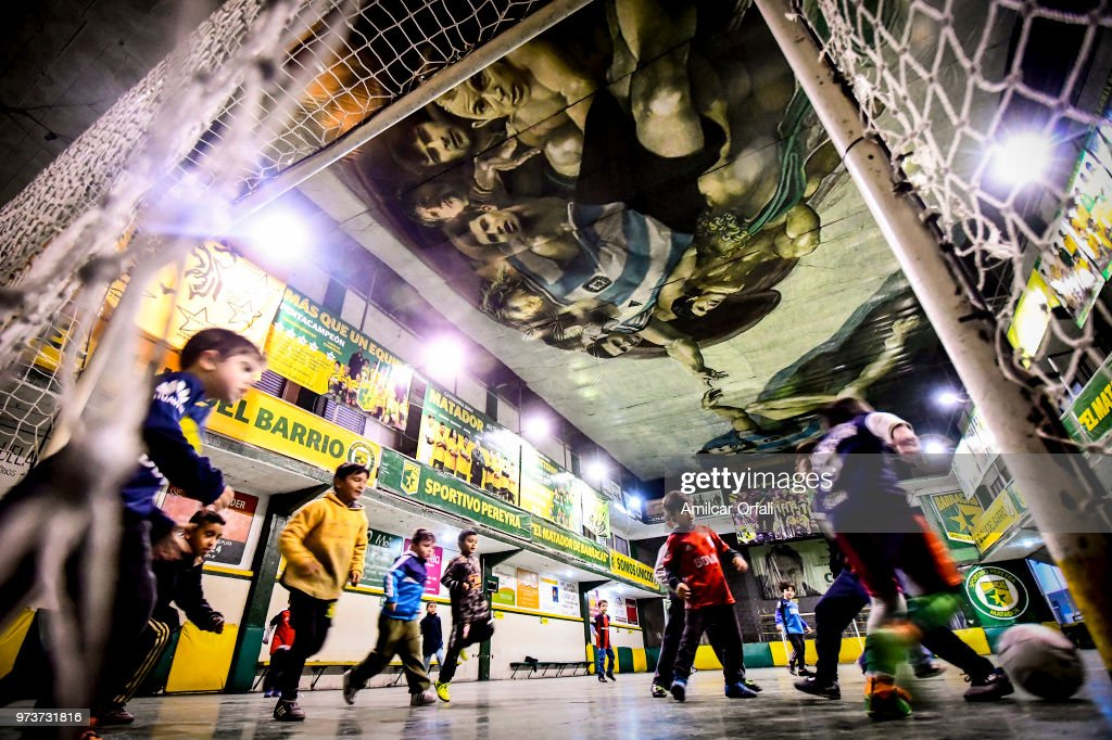 Kids play at the pitch of Sportivo Pereyra de Barracas club on June 13, 2018 in Buenos Aires, Argentina. The mural was painted in the ceiling of the pitch by local artist Santiago Barbeito depiciting the 'Creation of Adam' and making a tribute to Argentine football stars.