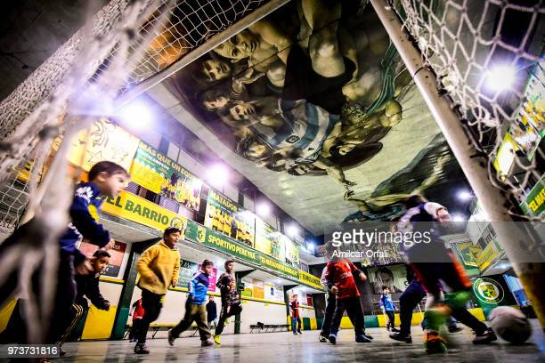 Kids play at the pitch of Sportivo Pereyra de Barracas club on June 13 2018 in Buenos Aires Argentina The mural was painted in the ceiling of the...