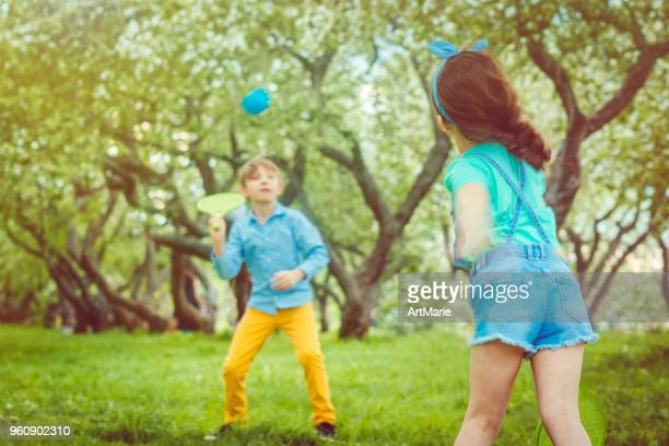 Kids play badminton or tennis outdoors