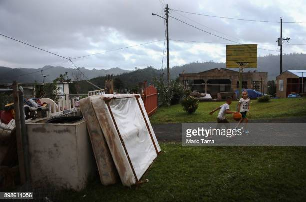 Kids play basketball next to storm debris still waiting to be collected on Christmas day on December 25 2017 in Morovis Puerto Rico Thirty percent of...