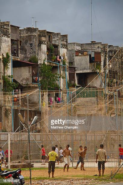 Kids play cricket and soccer in front of the apartment living areas in the slums of Phnom Penh, Cambodia