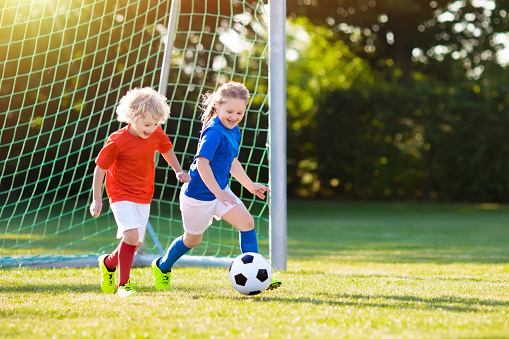 Kids play football. Child at soccer field. 1005387078