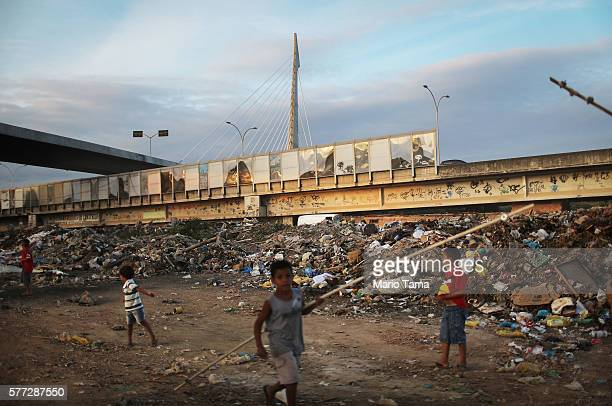 Kids play in a garbage dump area beneath a 'sound barrier' attached along a stretch of the main highway which links Rio's international airport to...