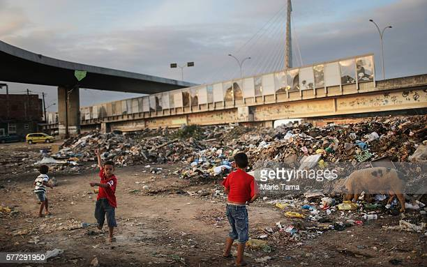 Kids play in a garbage dump area beneath a 'sound barrier' attached along a stretch of the main highway which links RioÕs international airport to...