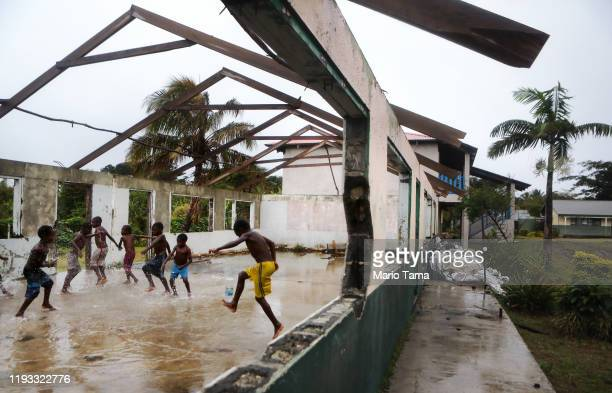 Kids play in the rain in a school building heavily damaged by Cyclone Pam during the first significant local rainfall in months in an extended dry...