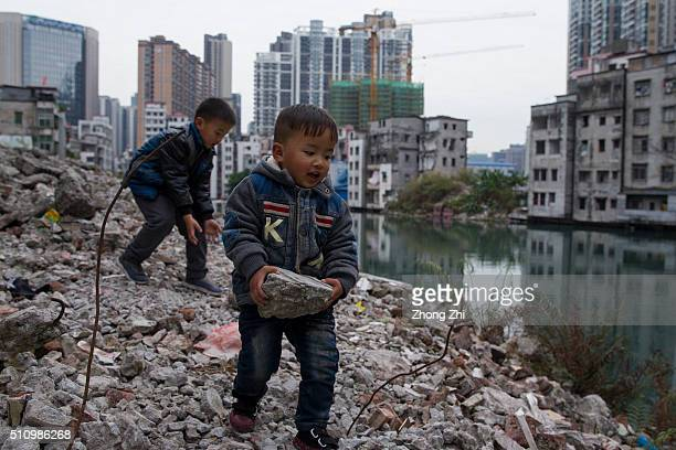 Kids play on the ground near demolished residential buildings in Xiancun a urban village in the Zhujiang New Town district of Guangzhou as high...