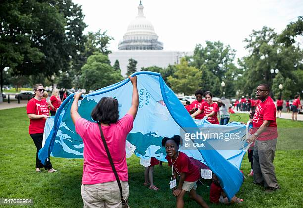 Kids play under a fabric map of the world during the Moms Clean Air Force playin for climate action in Upper Senate Park on Wednesday July 13 2016