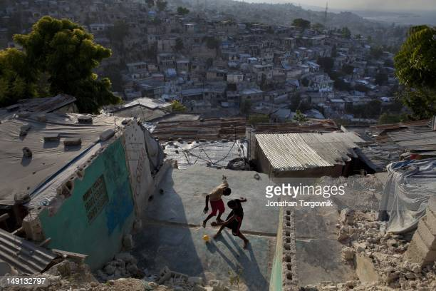 Kids play with a ball amongst ruins of a building that was destroyed during the earthquake on the hills surrounding PortauPrince January 2011 in...