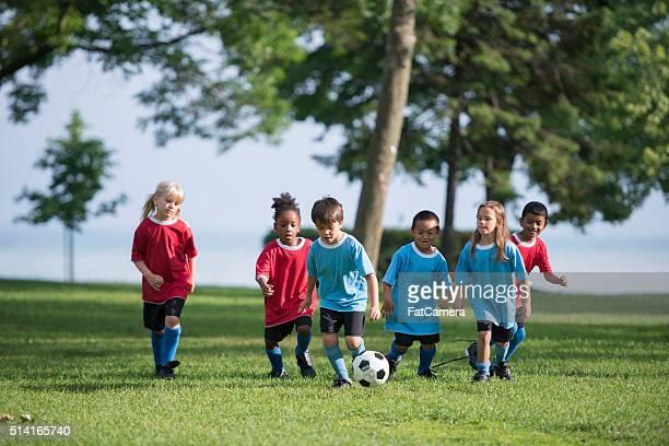 Kinder spielen mit einem Fußball
