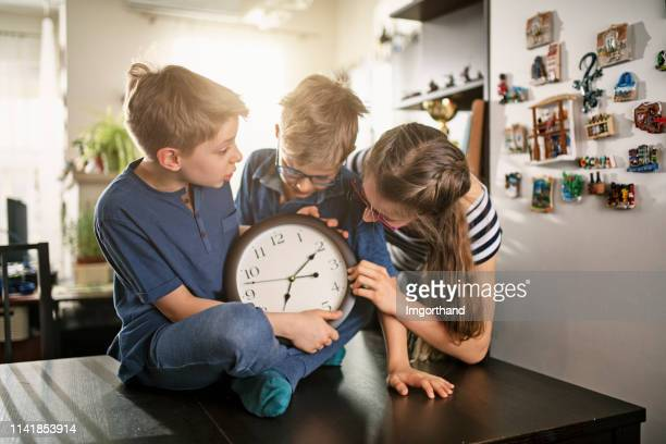kids playing an april fools day prank - daylight saving time stock pictures, royalty-free photos & images