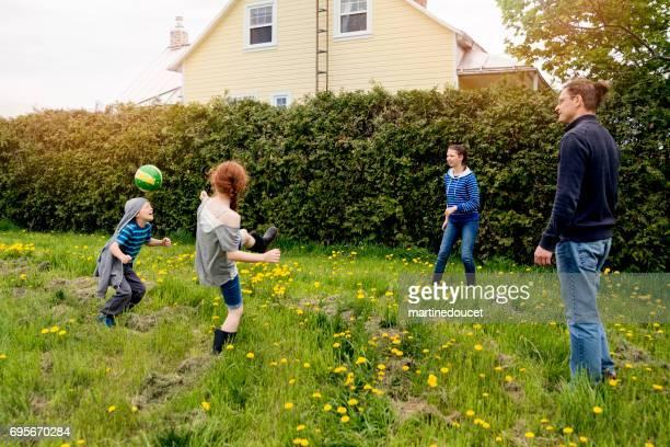 Kinder spielen Ball im Freien mit Papa um Haus.