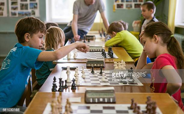 Kids playing chess, indoors