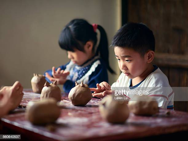 Kids playing clay and making pottery