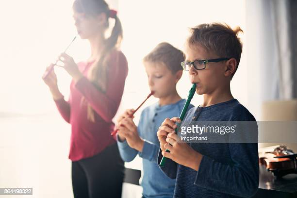 Kids playing flutes together in music class