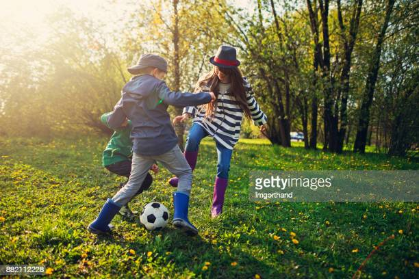 Kids playing football in city park on spring day