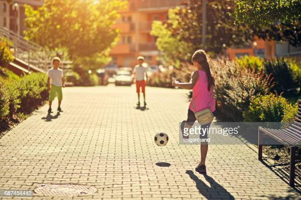 kids playing football in residential area - public park stock photos and pictures