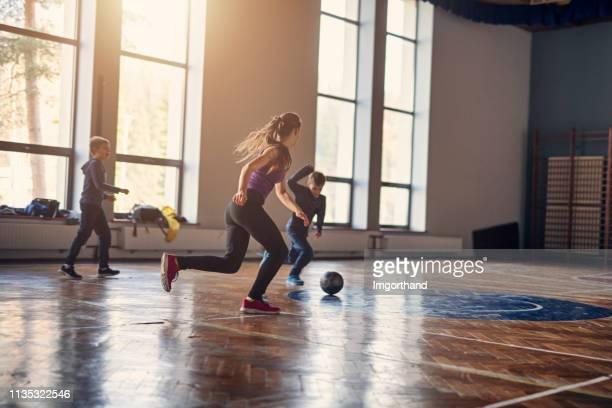 niños jugando al fútbol en el gimnasio de la escuela - patio de colegio fotografías e imágenes de stock