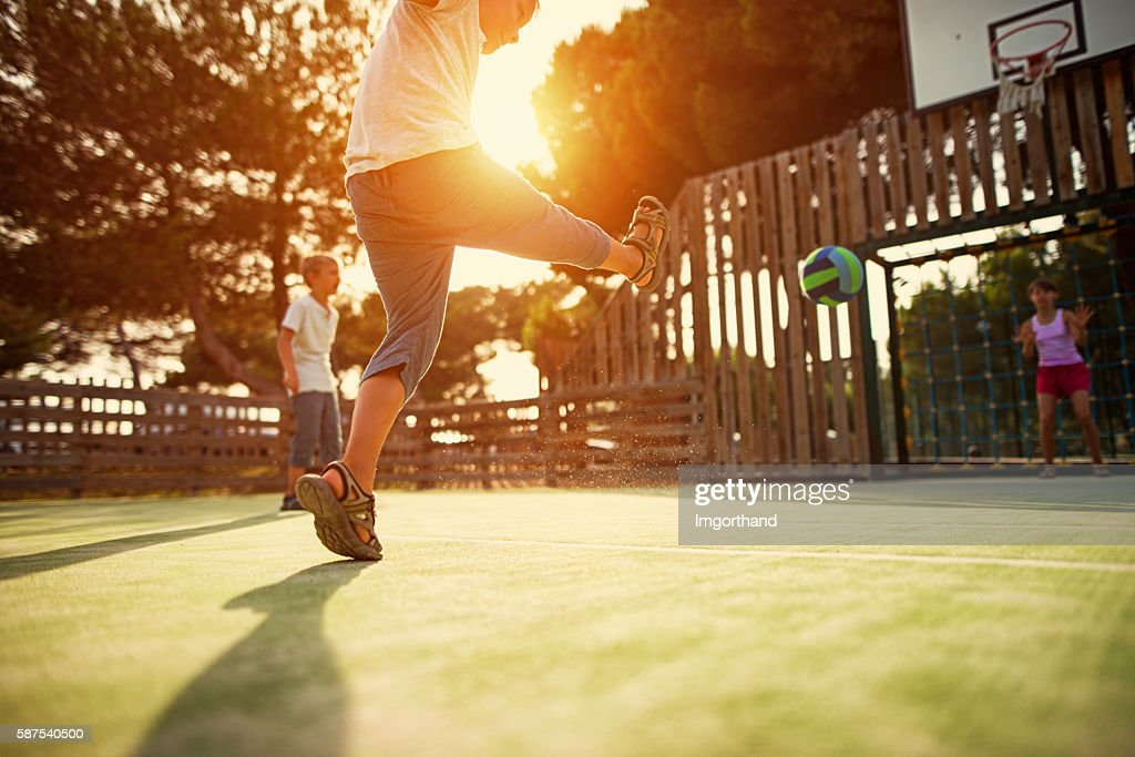 Kids playing football in the schoolyard : Stock Photo