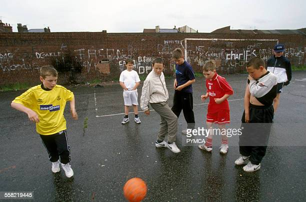 Kids playing football on a concrete football pitch UK 2000