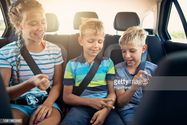 kids playing games in car during road trip - family inside car stock photos and pictures