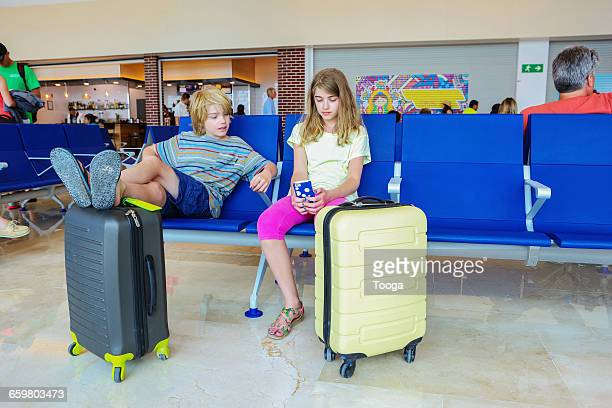 Kids playing games on smartphone at airport