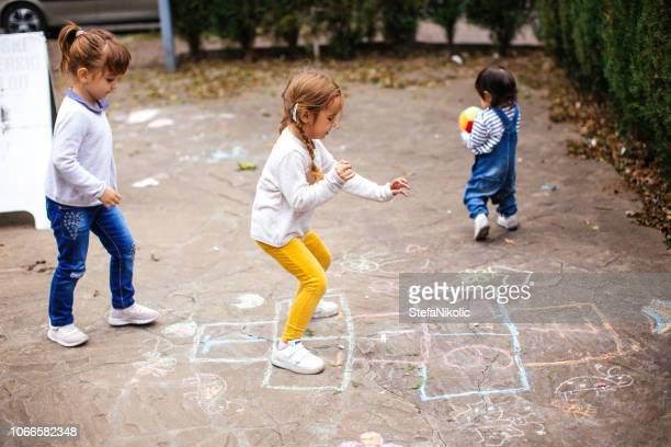 kids playing hopscotch on playground outdoors - hopscotch stock pictures, royalty-free photos & images