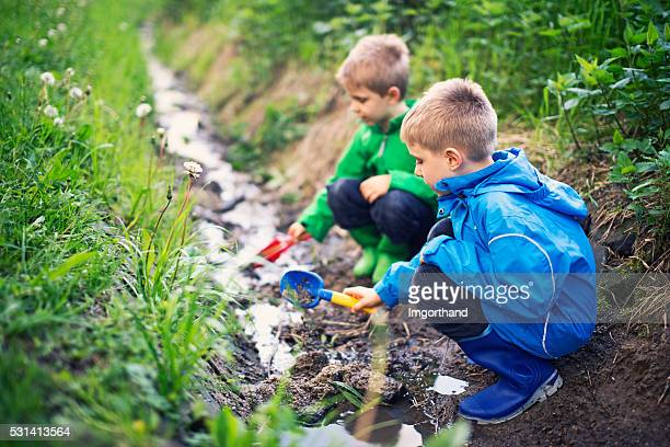 Kids playing in a drain trench stream
