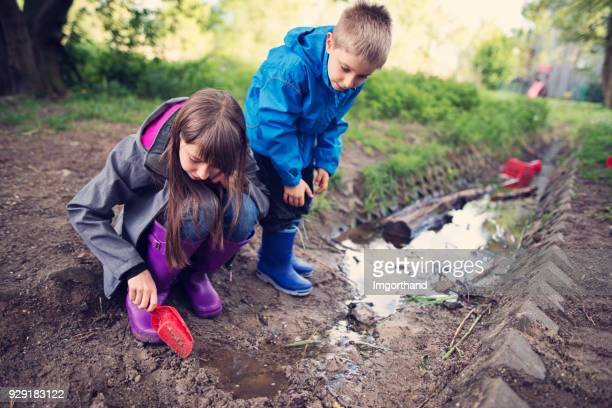 Kids playing in a puddle in drain trench