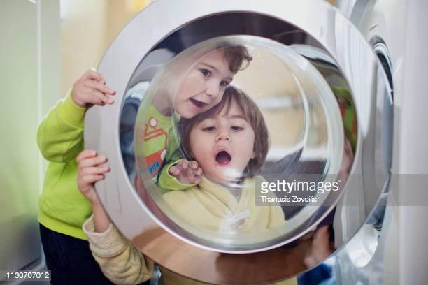 kids playing in front of a washing machine - waschmaschine stock-fotos und bilder