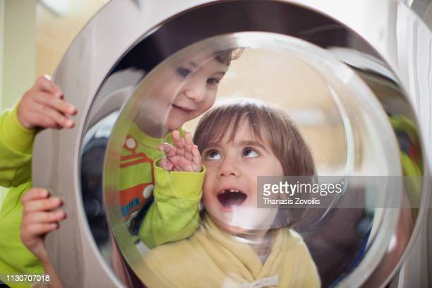 Kids playing in front of a washing machine