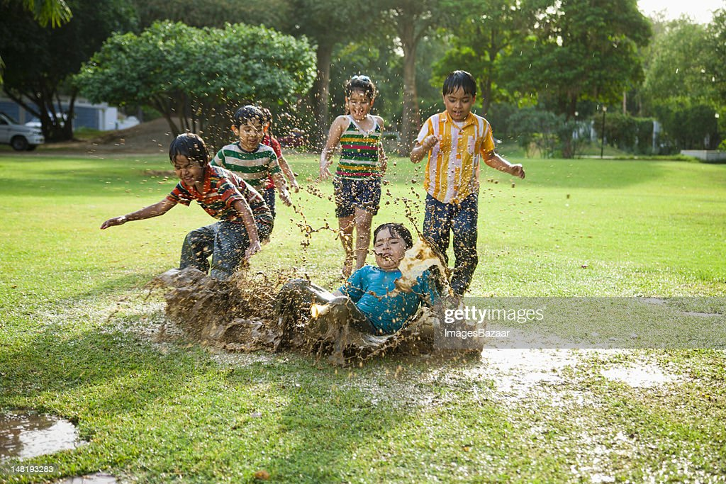 Kids (4-7) playing in puddle of water : Stock Photo