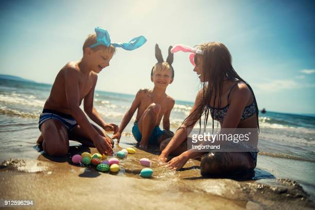 kids playing in sea during easter - easter beach stock pictures, royalty-free photos & images