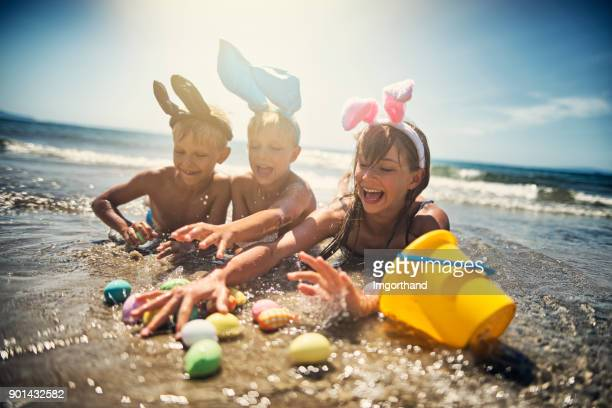 kids playing in sea during summer easter - easter egg stock pictures, royalty-free photos & images