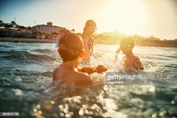Kinder spielen im Meer bei Sonnenuntergang