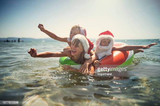 kids playing in sea on swim ring during summer christmas - beach christmas stock pictures, royalty-free photos & images