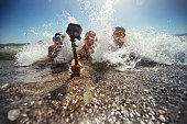Kids playing in sea waves and filming themselves using waterproof action camera.