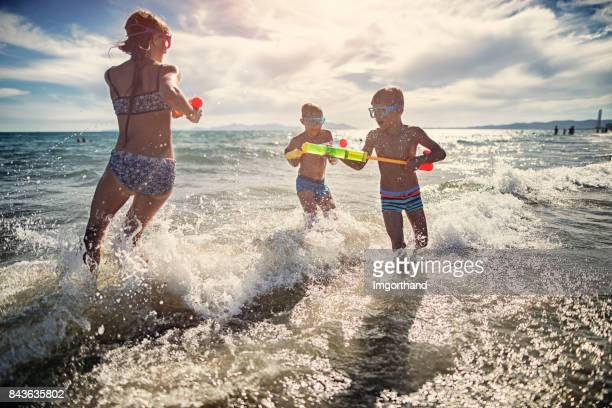 Kids playing in sea with water guns
