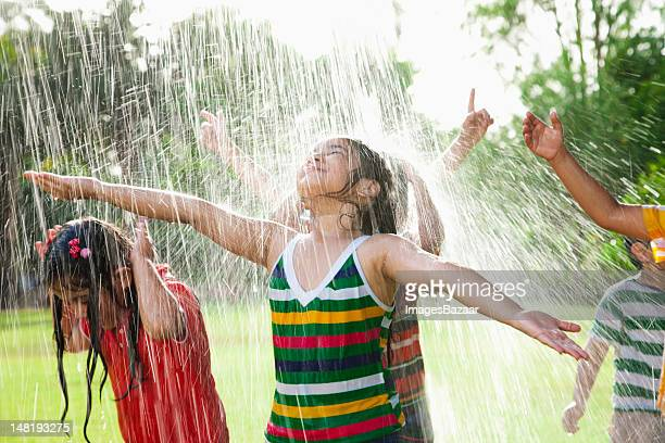 Kids (4-7) playing in spray of water on grass