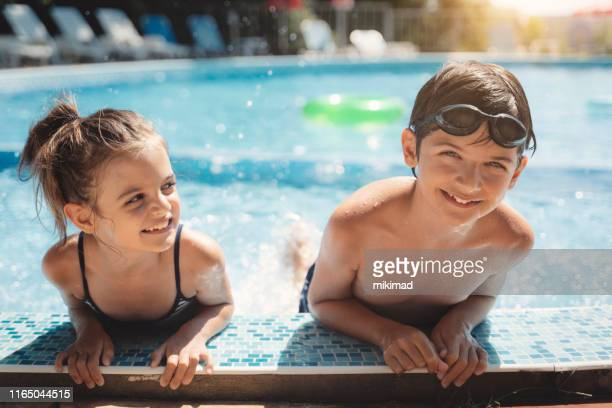 kids playing in swimming pool. children swim. family fun. - kids pool games stock pictures, royalty-free photos & images