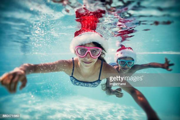 Kids playing in swimming pool during summer Christmas