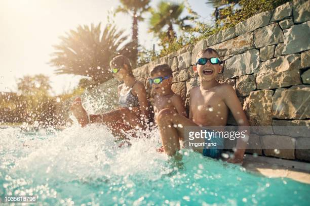 kids playing in swimming pool - tourist resort stock pictures, royalty-free photos & images