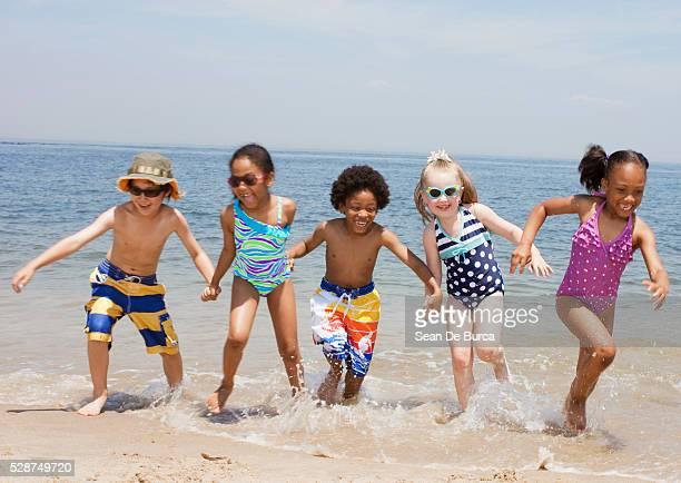 kids playing in the surf - somente crianças - fotografias e filmes do acervo