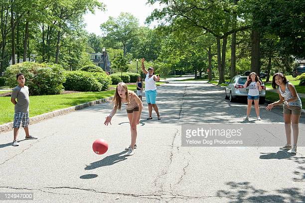 kids playing kickball in a suburban neighborhood - kickball stock photos and pictures