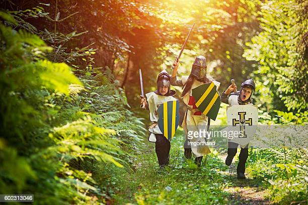 Kids playing knights in forest
