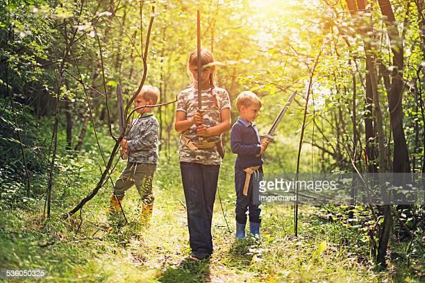 Kinder spielen im sonnigen Wald knights