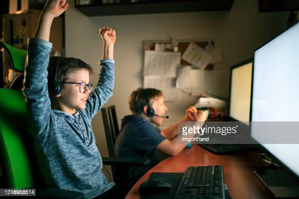 kids playing multiplayer online games using desktop pc - esports stock pictures, royalty-free photos & images