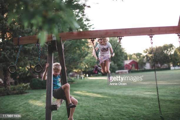 kids playing on backyard jungle gym - ジャングルジム ストックフォトと画像