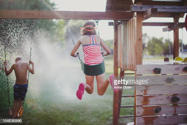 kids playing on backyard swing set - annie sprinkle stock pictures, royalty-free photos & images