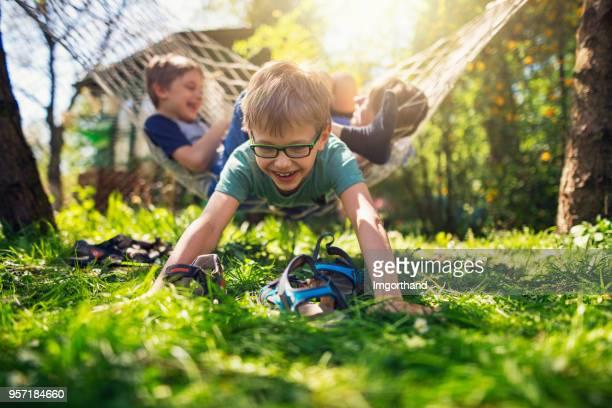 kinderen spelen op hangmat in de achtertuin - 10 11 jaar stockfoto's en -beelden